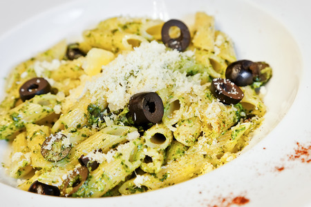 Penne with olives, parmesan cheese and greens photo
