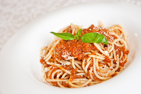 Spaghetti Bolognese with parmesan cheese and basil twig photo