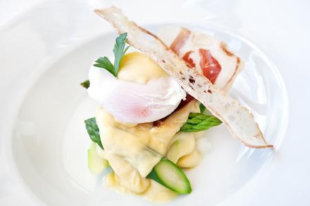Baked asparagus with hollandaise sauce, poached egg and parma ham Standard-Bild