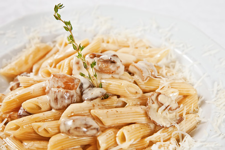 Penne with porcini mushrooms, parmesan cheese and rosemary twig photo