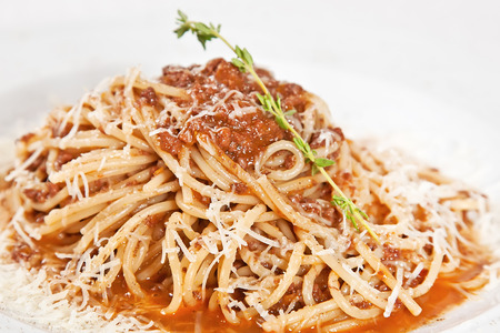 Spaghetti Bolognese with parmesan cheese and rosemary twig photo