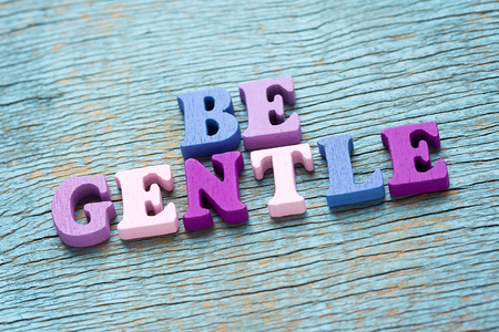 Be gentle phrase made of wooden colorful letters on vintage background