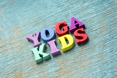 Yoga kids phrase made of wooden colorful letters on vintage background