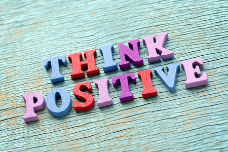 positivity: Think positive phrase made of wooden colorful letters on vintage background