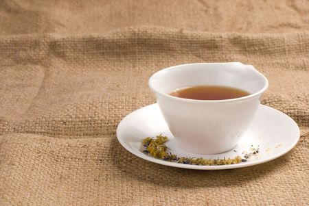 fibrous: Red tea in white ceramic cup with burlap background