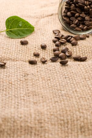 Coffee beans in glass jar on brown burlap background photo