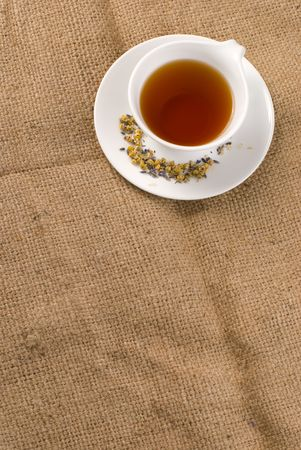Red tea in white ceramic cup with burlap background photo