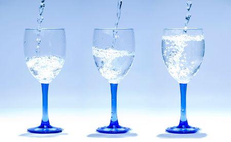 gradually: three glasses gradually full of water in order Stock Photo