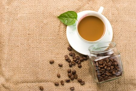 fresh coffee with beans in glass jar on linen background photo