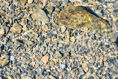 In the river, pebbles under water with reflecting light photo
