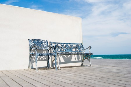 Bench on wooden floor with white wall in the beach. photo