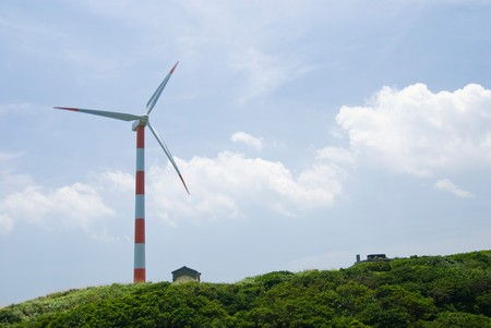 clean energy concept.  wind turbine in green hill under cloudy blue sky.  Stock Photo - 7723038