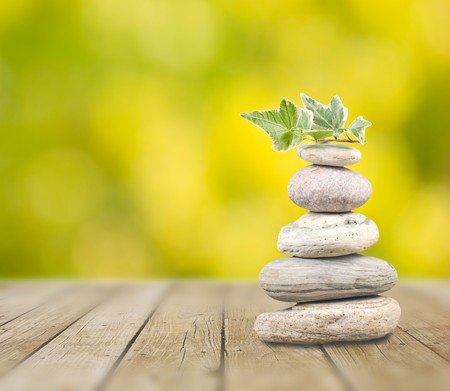 Stack pebbles on wooden table with green background Stock Photo - 7957547