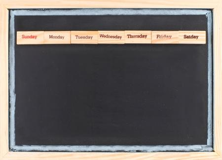 Monthly calendar with week words print on wood on blackboard photo