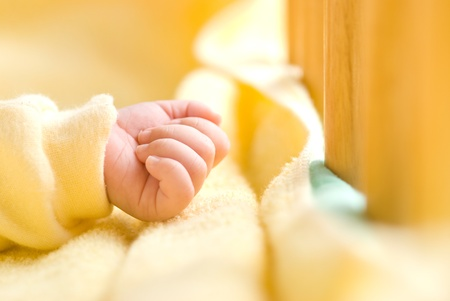 clench: Lovely little clenched hand, infant hand in baby bed with wooden fence.  Stock Photo