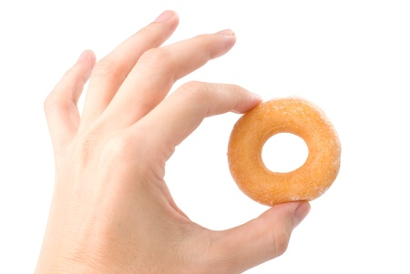 Lovely mini donut in mans hand isolated on white background photo