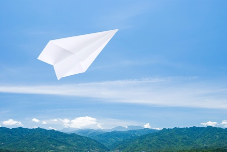 Paper airplane flying upon the mountain toward sky photo