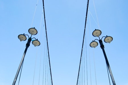 Street lamps under blue sky on the side of suspending bridge photo