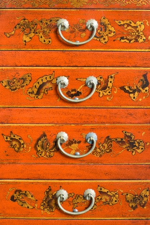 Old Chinese cabinet with traditional painting and handles  photo