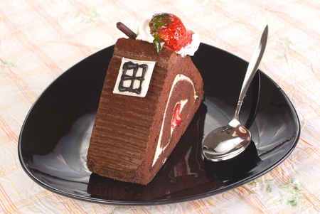 Piece of chocolate cake with strawberry in black  plate on the table photo