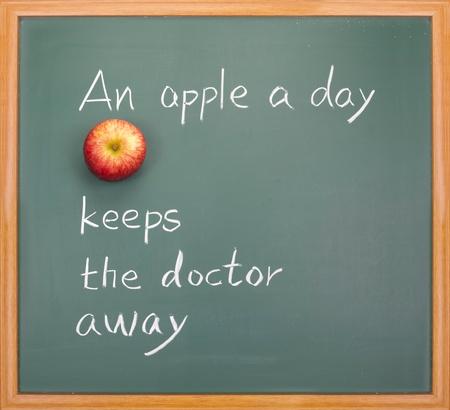 keeps: An apple a day keeps the doctor away, words on blackboard.