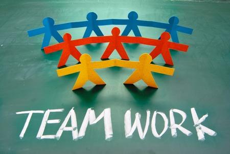 trabajo de equipo: Palabras de trabajo en equipo y mu�ecos de papel colorido en pizarra