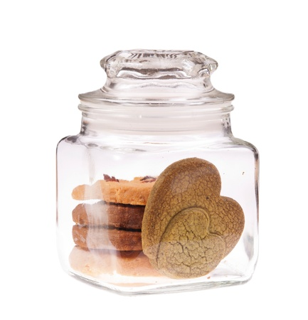 two heart pattern cookies in transparent glass jar, isolated on white background. Made up of chocolate. photo