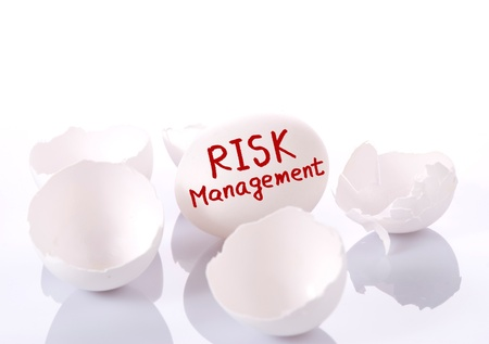 savings risk: Risk management. Egg and broken eggshells on white background  Stock Photo