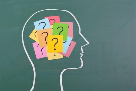 人間の脳とカラフルな疑問符を黒板に描画します。 写真素材