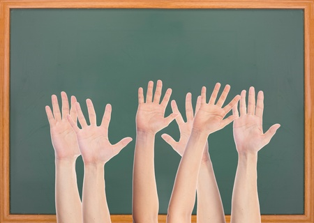 Many hands rise in front of blank blackboard photo