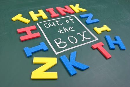 out think: Piense fuera de la caja, las palabras de colores en la pizarra. Foto de archivo
