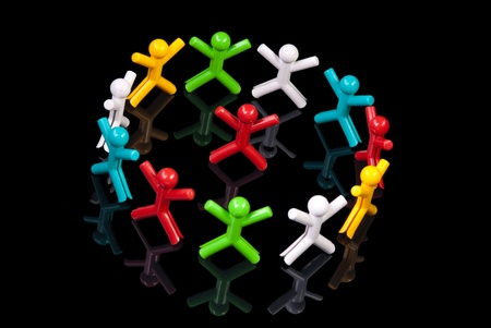 Team work concept. Colorful dolls on black background. Stock Photo - 10769748
