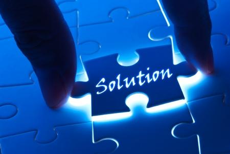 Oplossing concept, oplossing woord op puzzelstukje met achtergrondverlichting Stockfoto