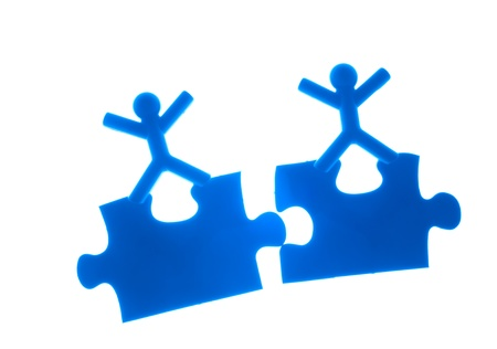 two piece: Two people rise hands and stand on the top of puzzles.
