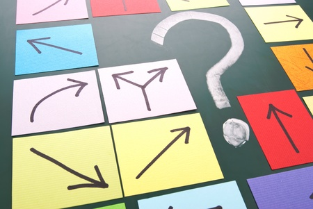uncertainty: Question mark and colorful paper with different direction. Stock Photo