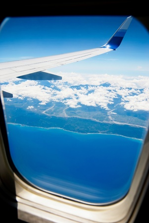 airfoil: View from airplane window. Airplane fly above the land and ocean.
