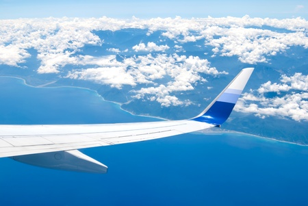 Airplane fly above the land and ocean Stock Photo