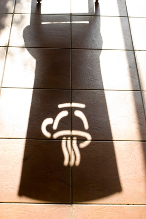 Shadow of coffee logo on the red brick floor photo