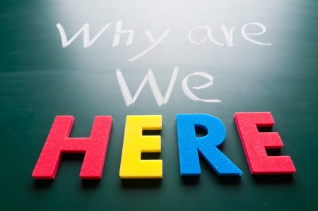 here: Why we are here, message words on blackboard