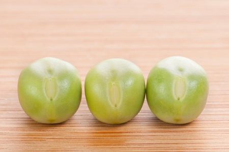 Three fresh green peas on wooden background photo