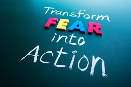 Transformar el miedo en concepto de acción, palabras de colores en la pizarra Foto de archivo