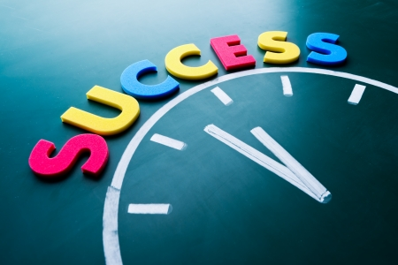 accomplishments: Time to success concept, color word and clock on blackboard