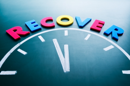 Time to recover concept, color word and clock on blackboard Stock Photo - 17711386