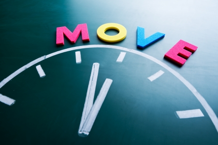 Time to move concept, color word and clock on blackboard photo