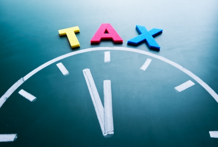 refund: Time for tax concept, color word and clock on blackboard