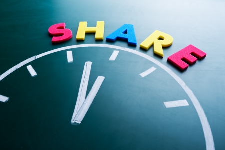 charitable: Time to share concept, color word and clock on blackboard