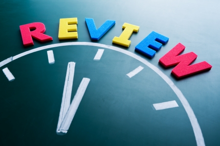 assessing: Time to review concept, color word and clock on blackboard Stock Photo