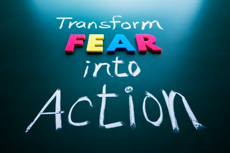 transform: Transform fear into action concept, colorful words on blackboard