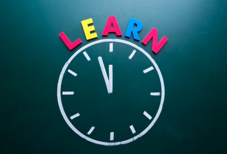 light classroom: Time to learn concept, color word and clock on blackboard Stock Photo
