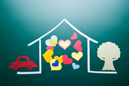 Family love concept, colorful heart shape in drawing house on blackboard. Paper cutting car and tree as decoration. photo
